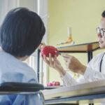 Man doctor neurologist is showing a elder female patient