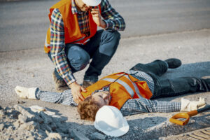 Worried man calling ambulance for his unconscious coworker