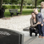 Young family visiting grave of family