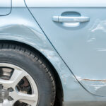 New silver Audi car with scratched and damaged paint near wheel and doors after crash accident and collision.