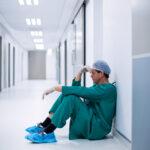 ensed male surgeon sitting in corridor