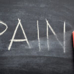 erasing pain, hand written word on blackboard being erased concept
